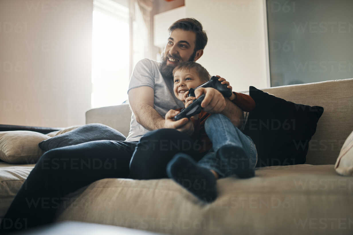 Father and son sitting together on the couch playing computer game - ZEDF01301 - Zeljko Dangubic/Westend61