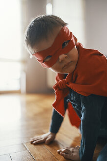 Little boy dressed up as a superhero crouching on the floor at home - ZEDF01319