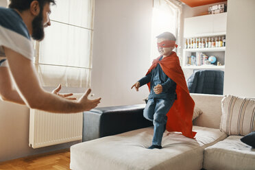Father playing with his little son dressed up as a superhero at home - ZEDF01322