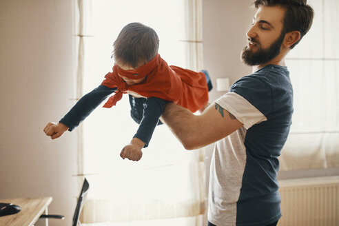 Father playing with his little son dressed up as a superhero - ZEDF01325