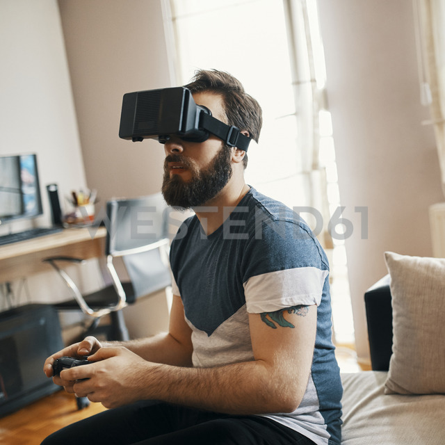 Man wearing virtual reality glasses at home playing computer game - ZEDF01328 - Zeljko Dangubic/Westend61