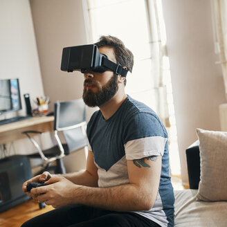Man wearing virtual reality glasses at home playing computer game - ZEDF01328