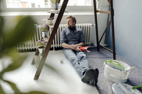 Man renovating room sitting on the floor having a rest - JOSF02160