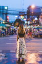 Thailand, Bangkok, young woman in the city standing on the street at night - AFVF00384