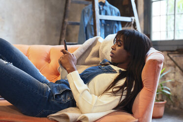 Young woman lying on the couch at home using cell phone - EBSF02307