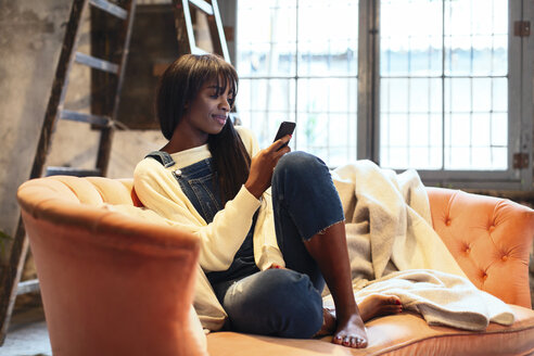 Smiling woman sitting on the couch at home using cell phone - EBSF02310