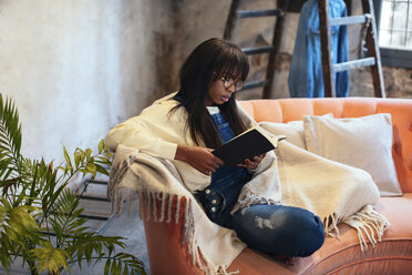 Young woman sitting on the couch at home reading book - EBSF02319