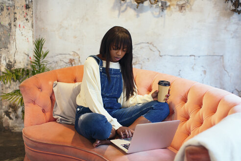 Young woman sitting on the couch with coffee to go in a loft using laptop - EBSF02325