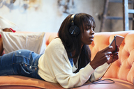 Young woman lying on the couch using tablet and headphones - EBSF02334