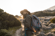 Italy, Sardinia, portrait of bearded hiker with hat and backpack - AFVF00399