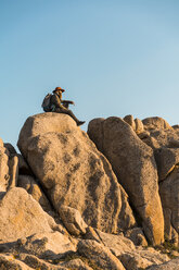 Italy, Sardinia, hiker with hat and backpack resting on a rock - AFVF00405
