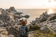 Italy, Sardinia, back view of hiker with backpack looking to the sea - AFVF00408