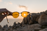 Man's hand holding sunglasses in front of evening sun, close-up - AFVF00411