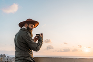 Italy, Sardinia, man taking photo with camera at sunset - AFVF00414