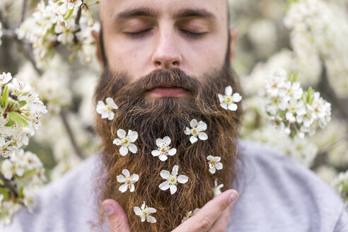 Portrait of hipster with white tree blossoms in his beard - AFVF00420