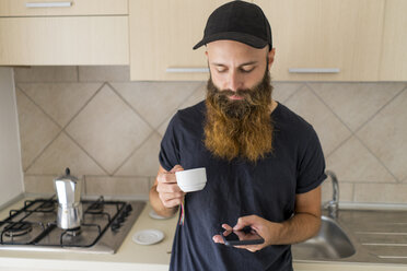 Bearded man standing in kitchen with espresso cup looking at cell phone - AFVF00429