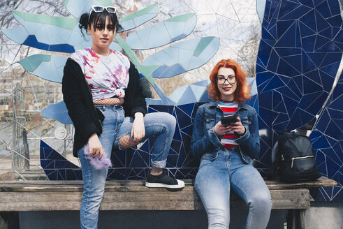 Portrait of hipster female friends holding mobile phones against mosaic wall - MASF01369