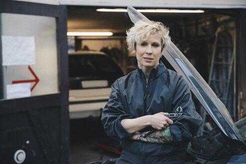 Portrait of confident mechanic leaning on car outside repair shop - MASF01372
