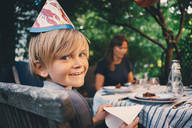 Portrait of happy boy wearing hat while holding tissue paper at garden dinner party - MASF01390