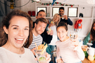 Portrait of friends with food and drinks enjoying in cottage during vacation - MASF01399