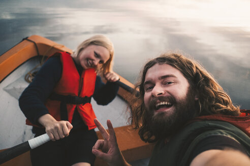 Portrait of happy couple sitting in boat on lake - MASF01414
