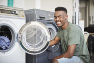 Portrait of smiling young man kneeling by washing machine at laundromat - MASF01423