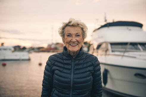 Portrait of happy senior woman standing at harbor during sunset - MASF01435