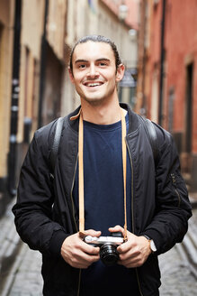 Portrait of smiling young man holding camera while standing in alley - MASF01447