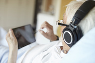 Over the shoulder view of senior man wearing headphones while using digital tablet in hospital - MASF01477