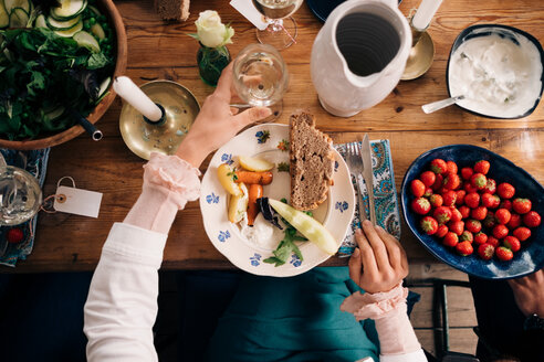 Midsection of woman holding wineglass while having healthy lunch in cottage - MASF01492