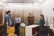 Multi-ethnic male and female business people with office equipment in elevator - MASF01525
