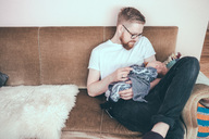 Mid adult man looking at baby boy while sitting on sofa - MASF01546