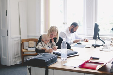 Mid adult businesswoman with baby girl working at table in creative office - MASF01579