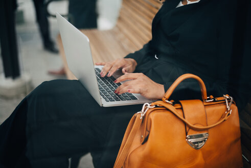 Midsection of businesswoman typing on laptop sitting at bus shelter seen from glass - MASF01591