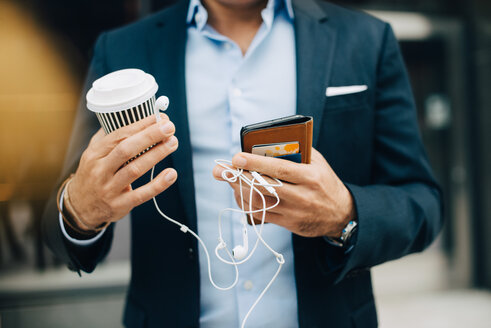Midsection of businessman holding smart phone with disposable coffee cup and in-ear headphones while standing in city - MASF01603