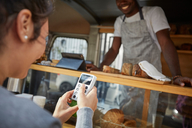 Mid adult woman using credit card reader to pay salesman at food truck - MASF01609