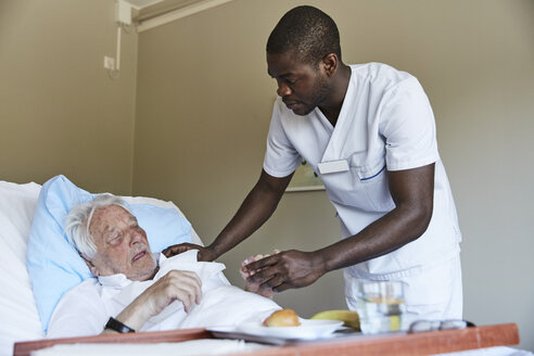 Male nurse giving cough syrup to senior man in hospital ward - MASF01648