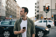 Man looking away while holding smart phone in city - MASF01657