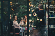 Man photographing young friends raising toast with wineglasses during dinner party - MASF01663