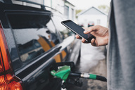 Man using mobile phone while refueling car at gas station - MASF01675