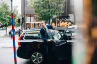 Mature businessman disembarking from taxi on street in city - MASF01687