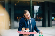 Mature businessman talking on mobile phone while carrying food and drinks in city - MASF01696