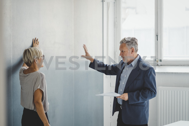 Mature businessman holding documents while discussing with female colleague in new office - MASF01708