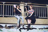 Hipster female friends taking selfie with mobile phones while sitting on wall against railing - MASF01712