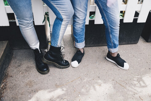 Low section of female friends wearing jeans while standing against fence - MASF01715