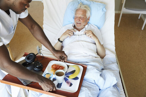 High angle view of male nurse serving breakfast to senior man in hospital ward - MASF01718