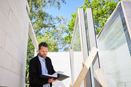 Low angle view of architect reading document while standing at construction site - MASF01721