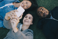 High angle view of smiling woman taking selfie with friends while lying on grass - MASF01733