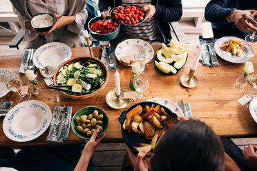 High angle view of men and women having food together in cottage - MASF01745