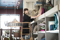 Low angle view of young female owner arranging cushions in rack while standing on ladder at store - MASF01748